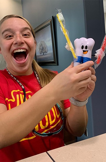 Dental team member holding fun toothbrush and toy