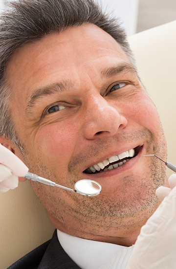Man's smile being examined for cavities